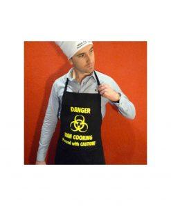 """Un set comprenant un tablier noir avec liens et une toque blanche ajustable avec l'inscription """"Danger Man Cooking""""."""