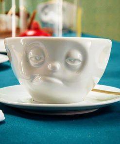 Une tasse à café au visage un peu fatigué